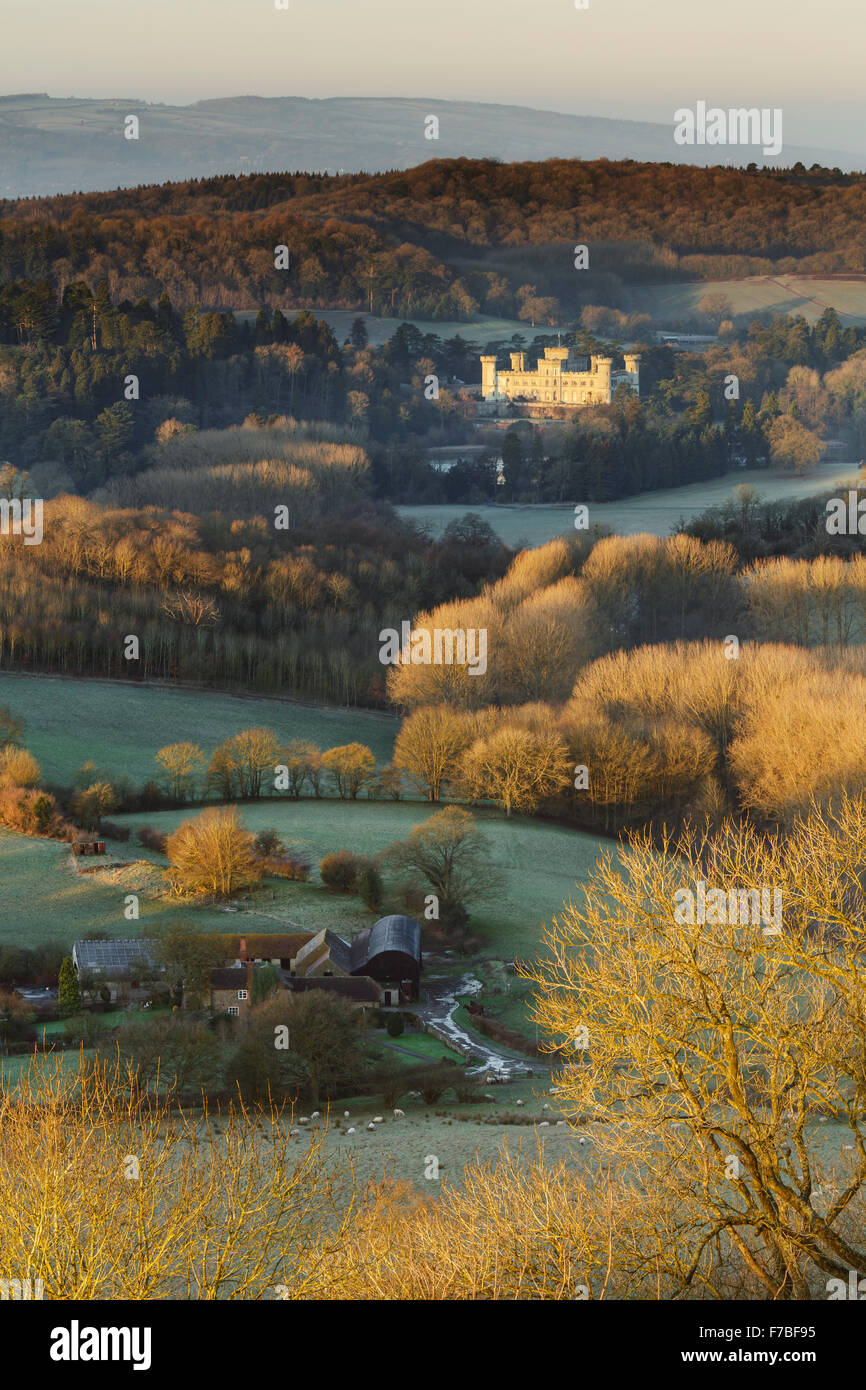 Sunrise lights up Eastnor Castle, Herefordshire. Frost on the bare trees makes them glow orange in the strong light. Stock Photo