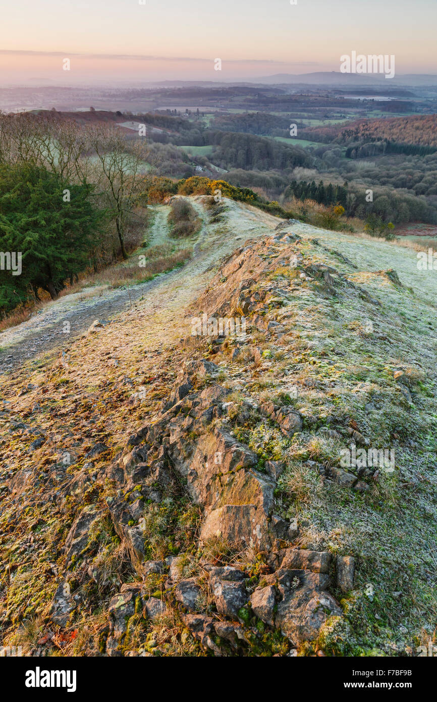 Sunrise lights up the footpath and rocks over Raggedstone Hill on the Malvern Hills, Herefordshire on a cold frosty Stock Photo