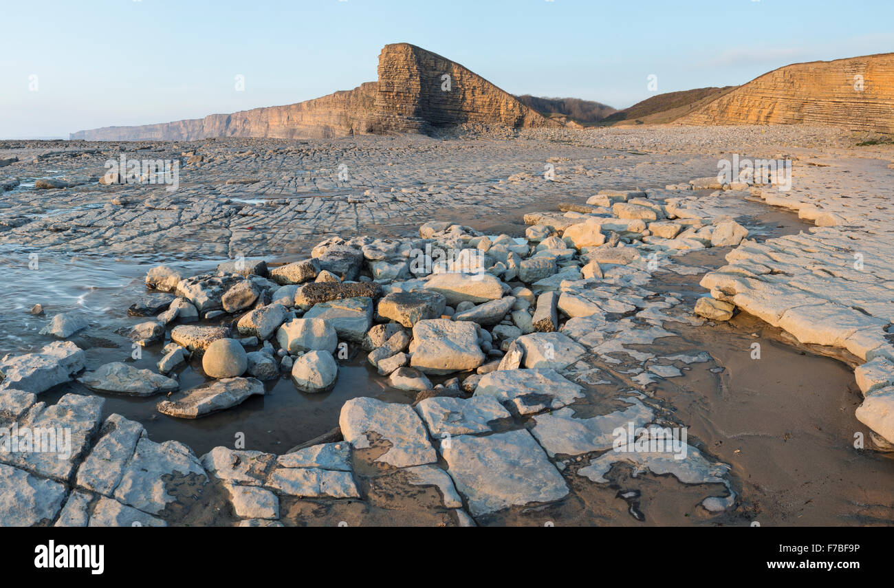 Beautiful rock formations at low tide at Nash Point, Vale of Glamorgan, Wales. The sunset is lighting up the cliffs Stock Photo