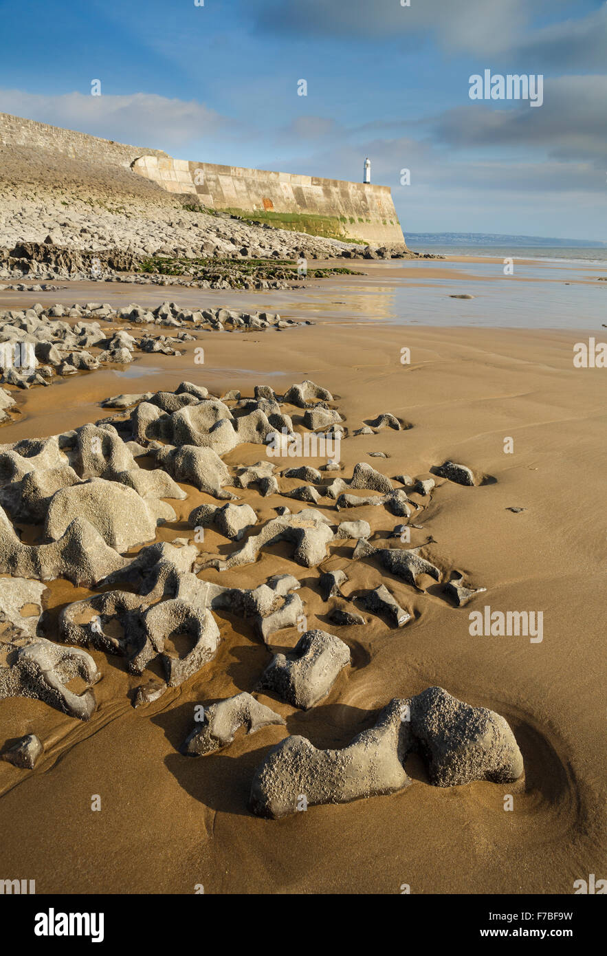 Beautiful rock formations at low tide at Porthcawl, Vale of Glamorgan, Wales. The sunset is lighting up the lighthouse Stock Photo