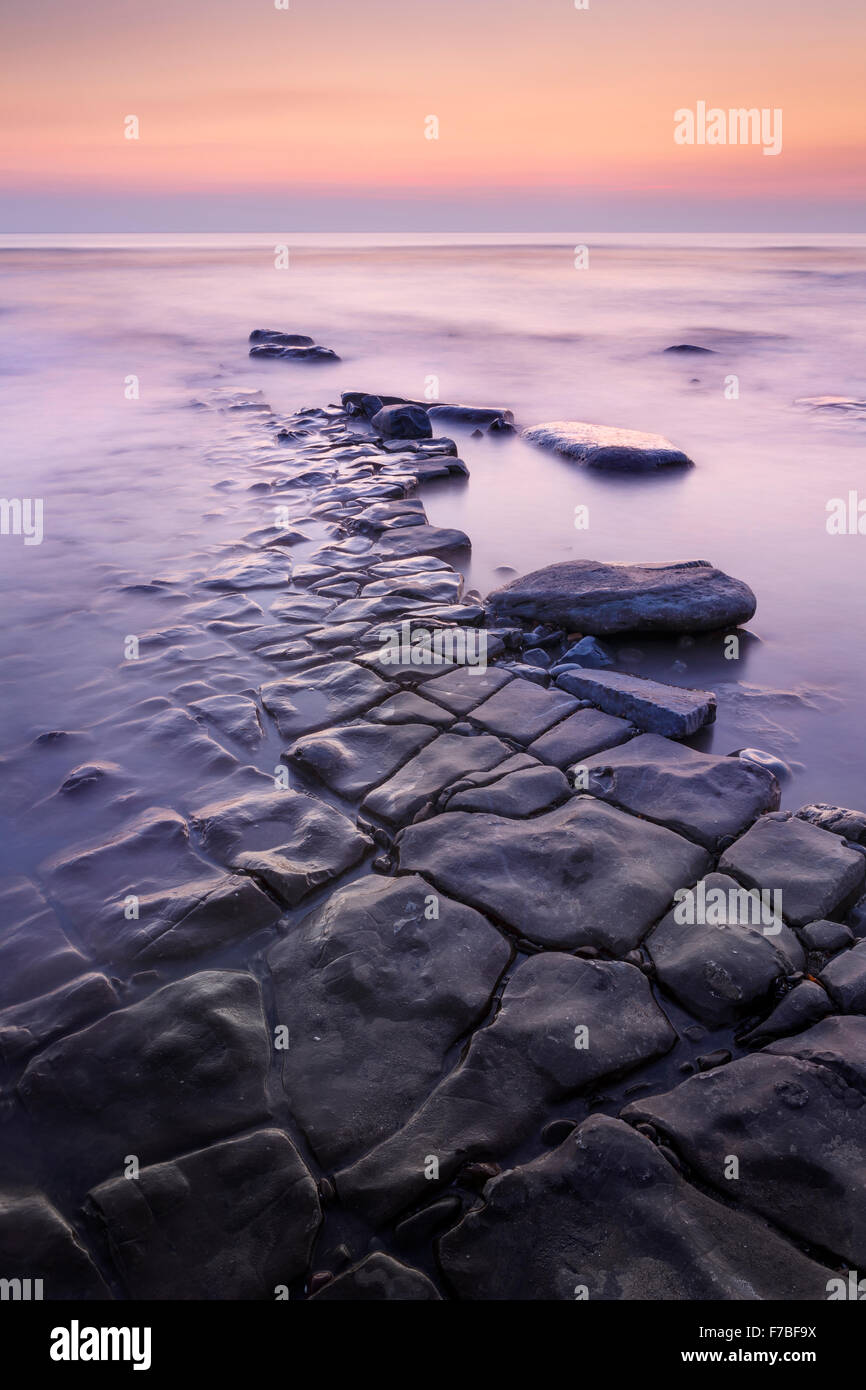 Beautiful rock formations lead into the sea at sunset at Southerndown, Vale of Glamorgan, Wales Stock Photo