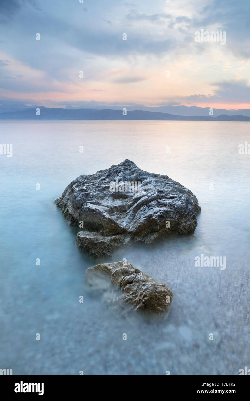 The pebbles and rocks on Kanoni beach, Kassiopi, Corfu are surrounded by the incoming tide. Stock Photo