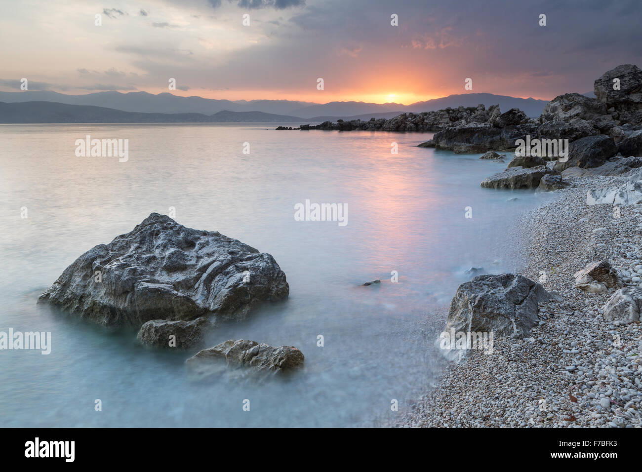 The pebbles and rocks on Bataria beach, Kassiopi, Corfu are lit up with the strong orange light of sunrise. Stock Photo