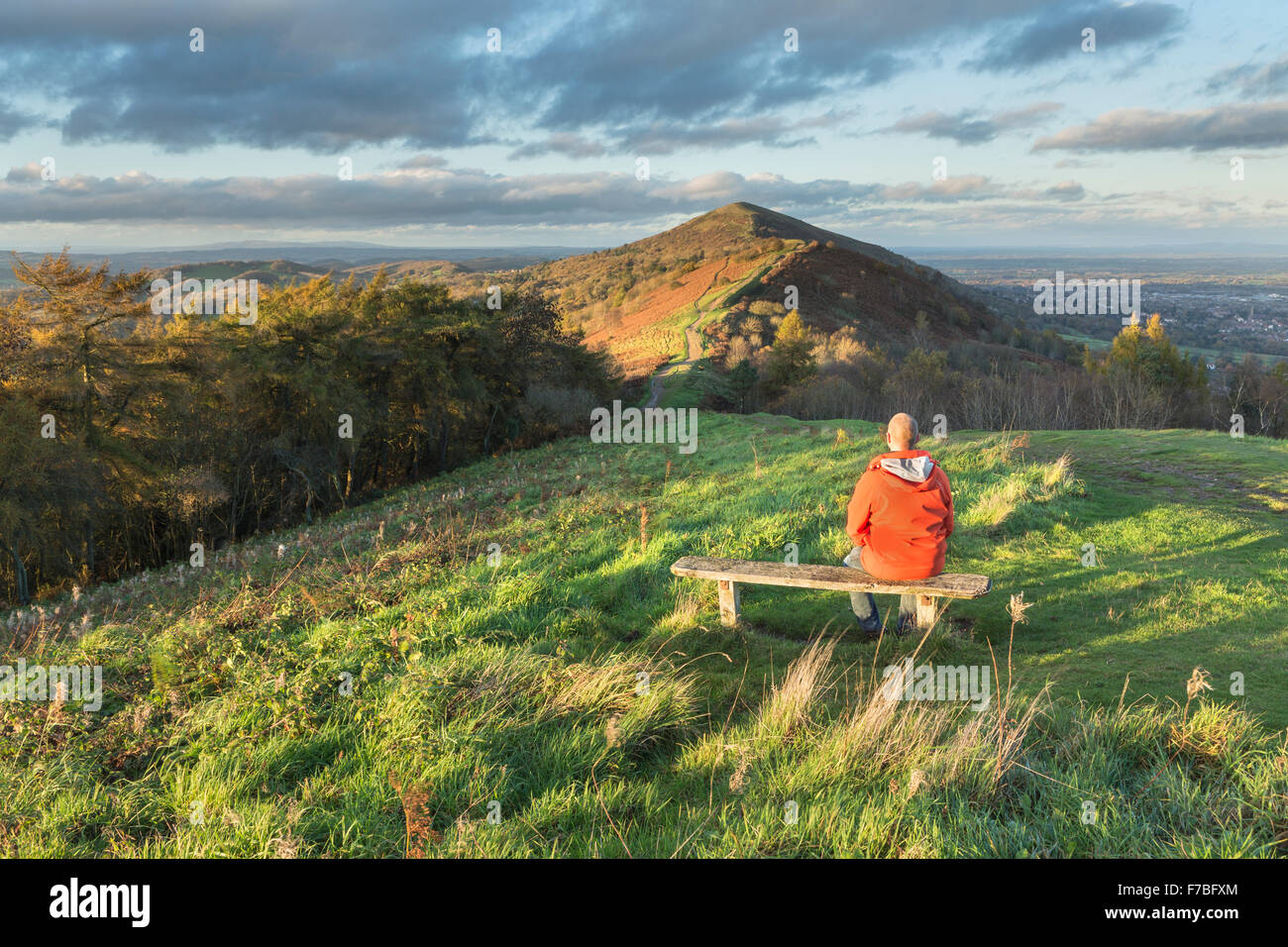 A walker in a bright orange coat sits on a wooden bench on Jubillee Hill to watch the beautiful sunset lighting Stock Photo