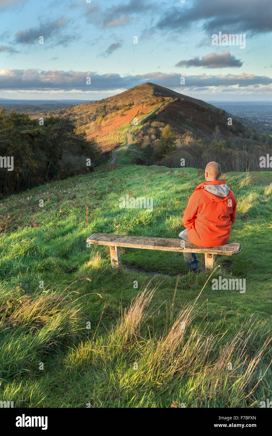 A walker in a bright orange coat sits on a wooden bench on Jubillee Hill to watch the beautiful sunset. Stock Photo