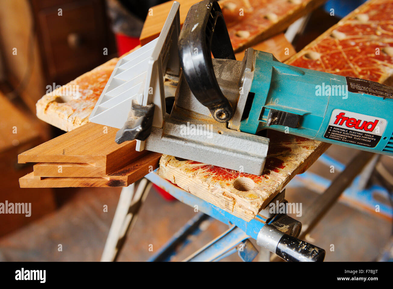 A biscuit jointer for cutting slots in a mitred wooden frame held in a workmate for jointing - Stock Image