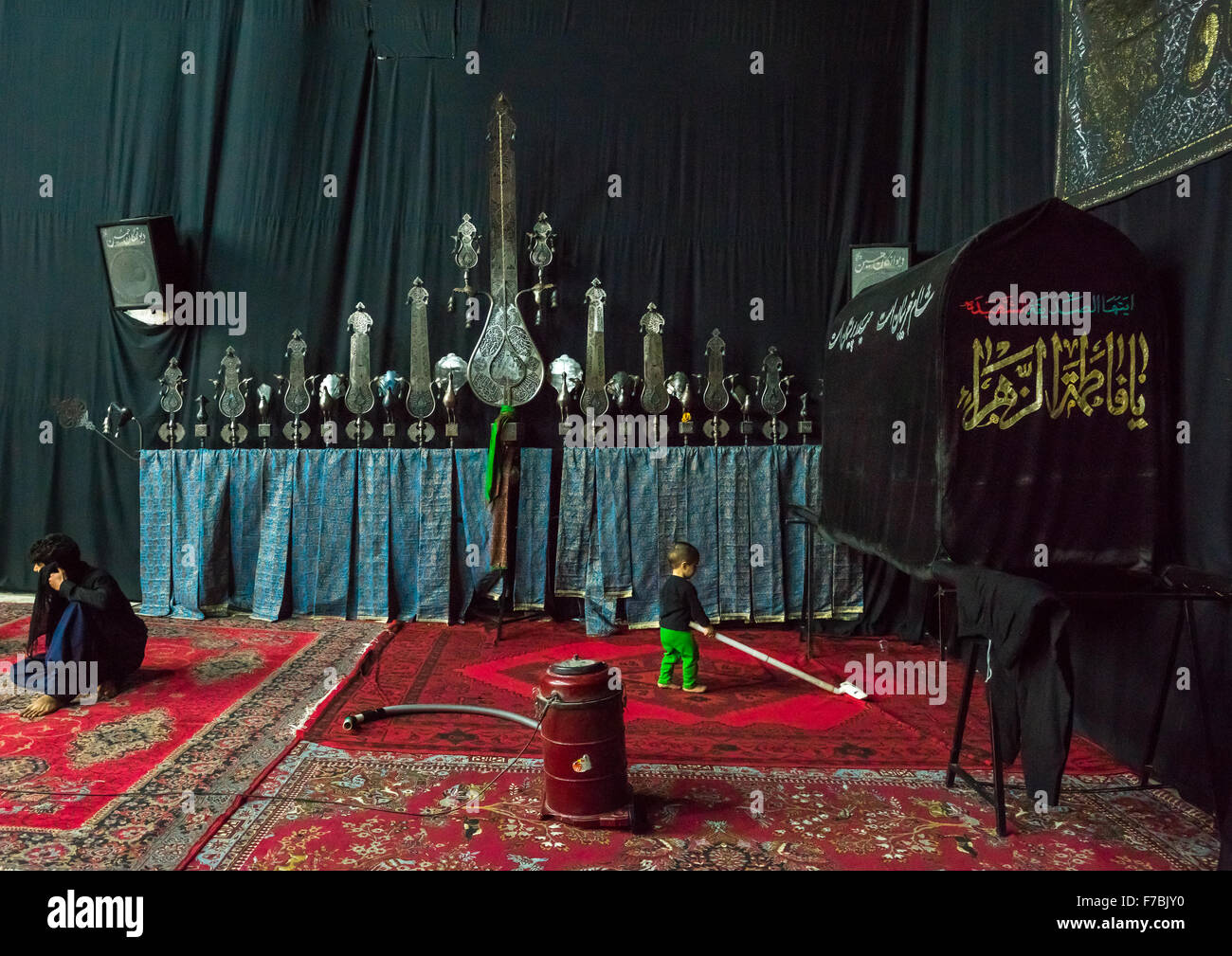 Little Boy Playing With An Aspirator In Front Of An Alam On Ashura, The Day Of The Death Of Imam Hussein, Isfahan - Stock Image