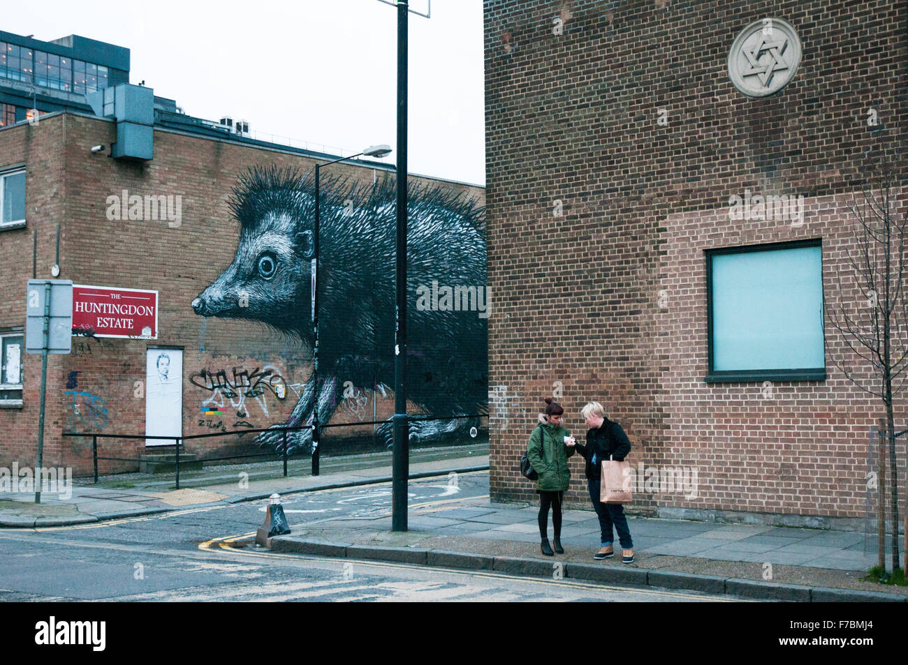 London,UK, 12 /2012.Two women on the street near a big rat mural painting in London East End. - Stock Image