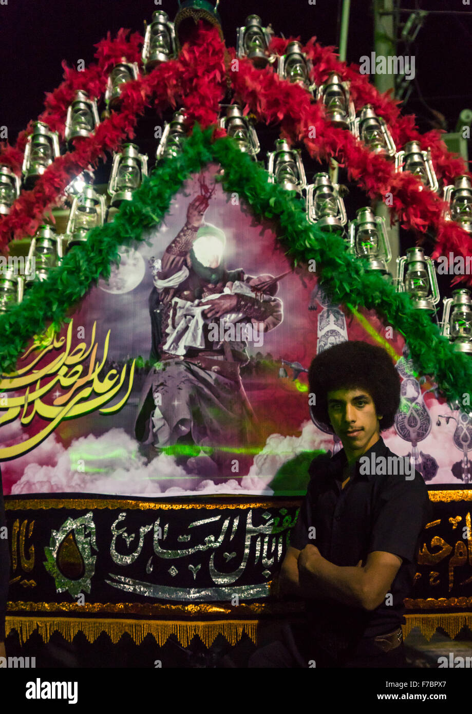 Young Iranian Shiite Muslim Man Mourner Pausing Proudly In Front Of An Alam On Ashura, The Day Of The Death Of Imam - Stock Image