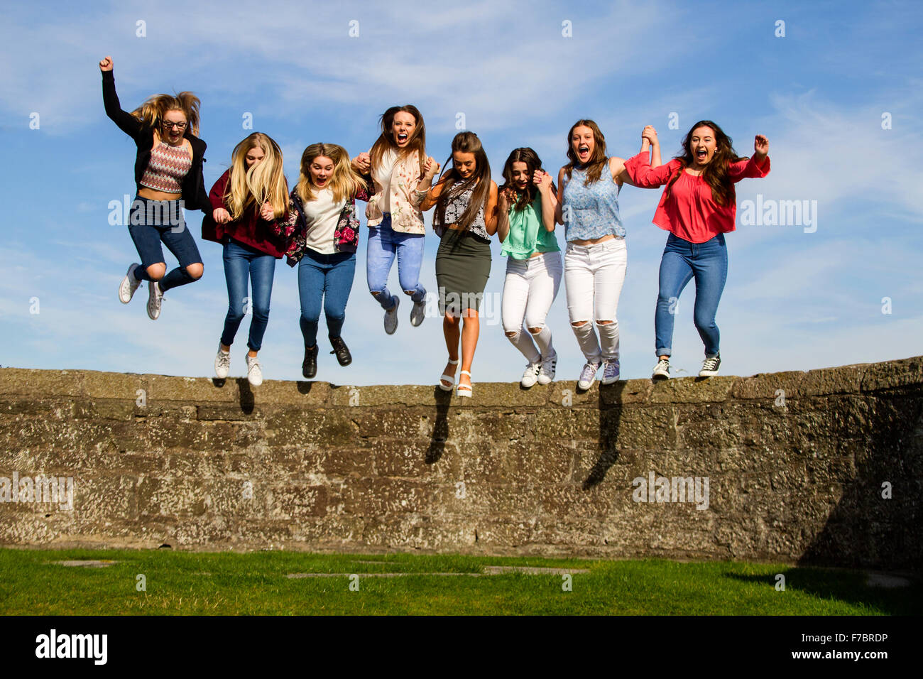 Eight teenage girls holding hands and jumping off the Broughty Ferry Castle wall in Dundee, UK Stock Photo
