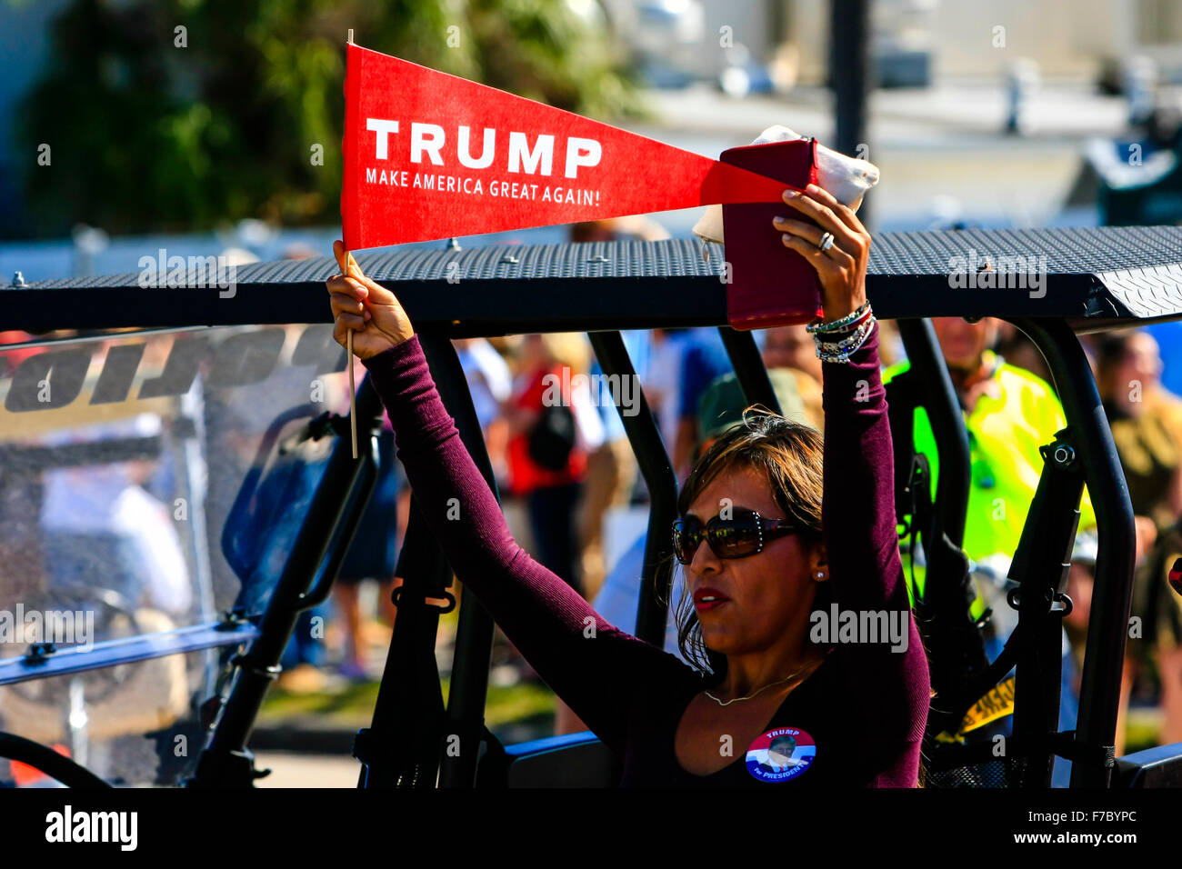 Hispanic woman holding a pro-Trump pennant showing her support by wearing t-shirts at his Presidential candidacy Stock Photo