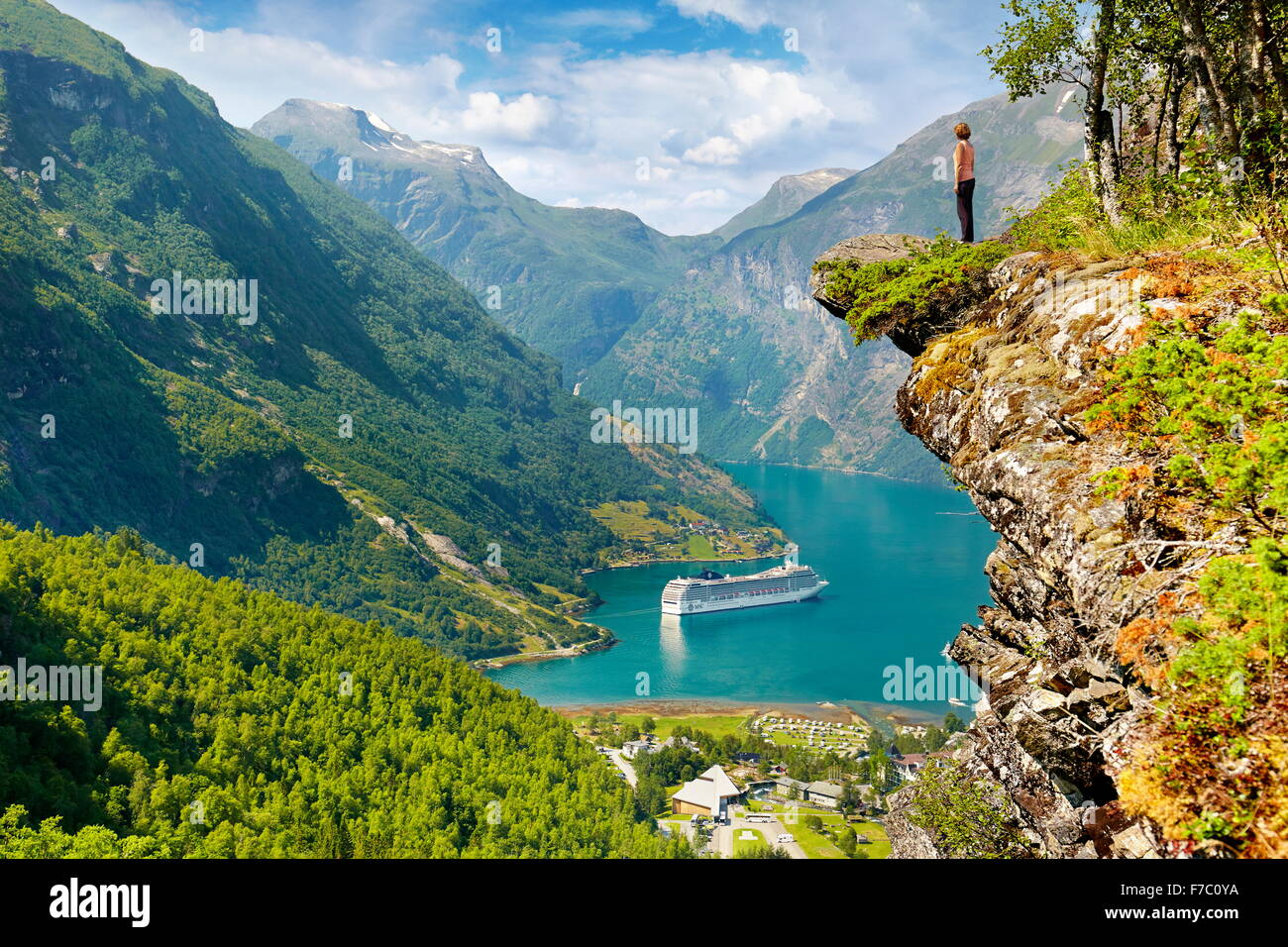 Tourist standing on the rock cliff, cruise ship in Geiranger Fjord in the background, Norway - Stock Image