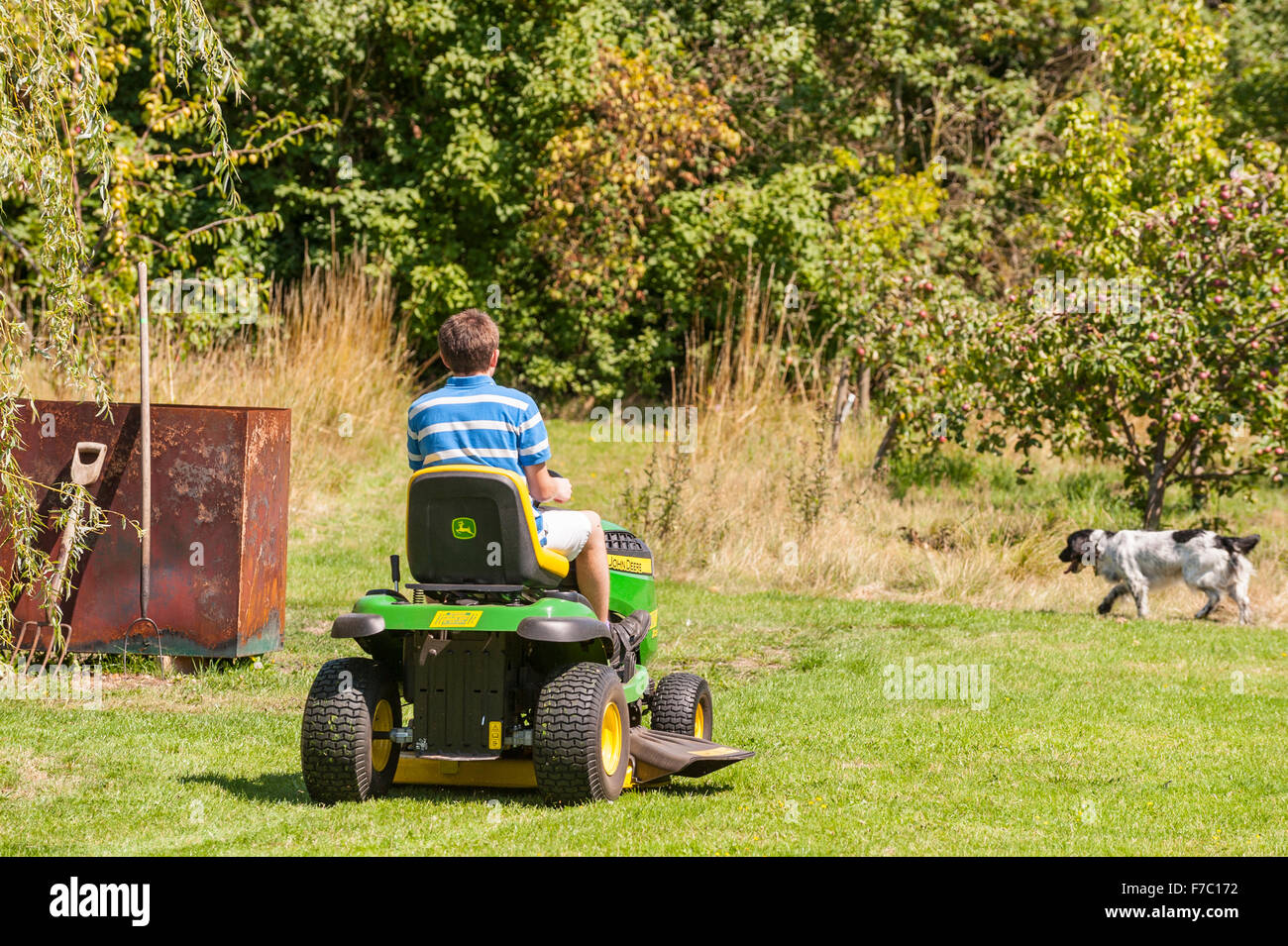 A 15 year old boy mowing the lawn on a John Deere ride on mower in the Uk - Stock Image