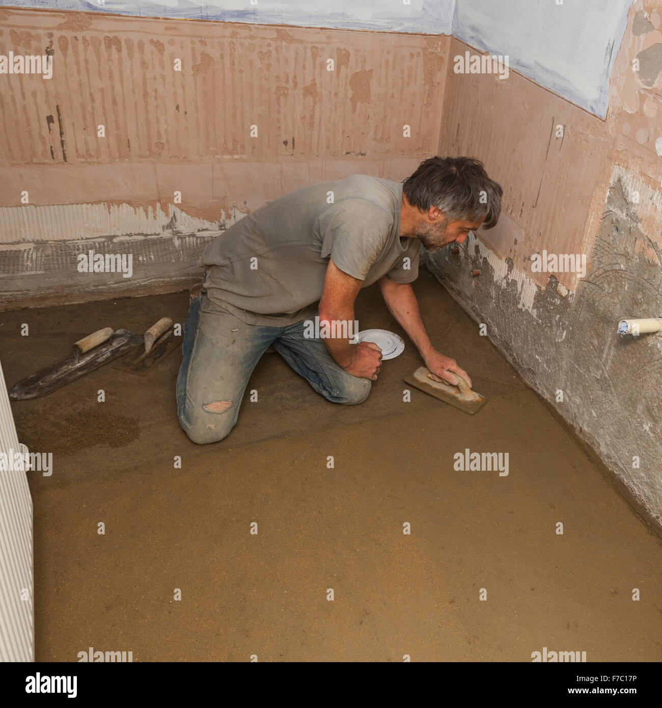 A builder floating up the top coat of a concrete floor in a bathroom Stock Photo