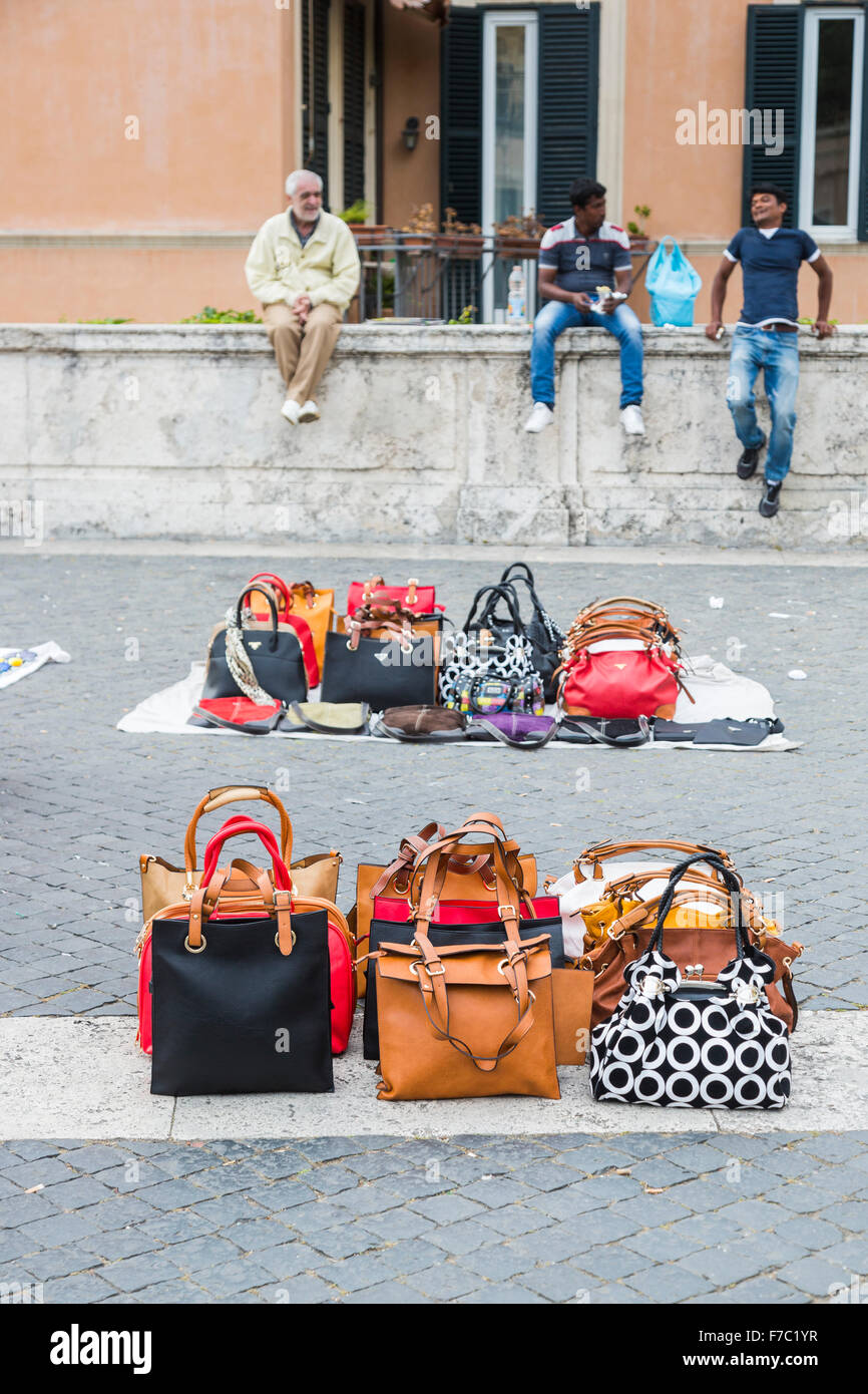 3d87bad187 Modern Roman lifestyle: Fake Prada and designer handbags laid out in the  road displayed on
