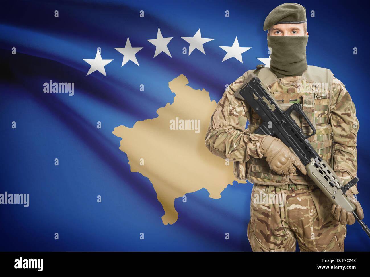 Soldier holding machine gun with national flag on background - Kosovo Stock Photo