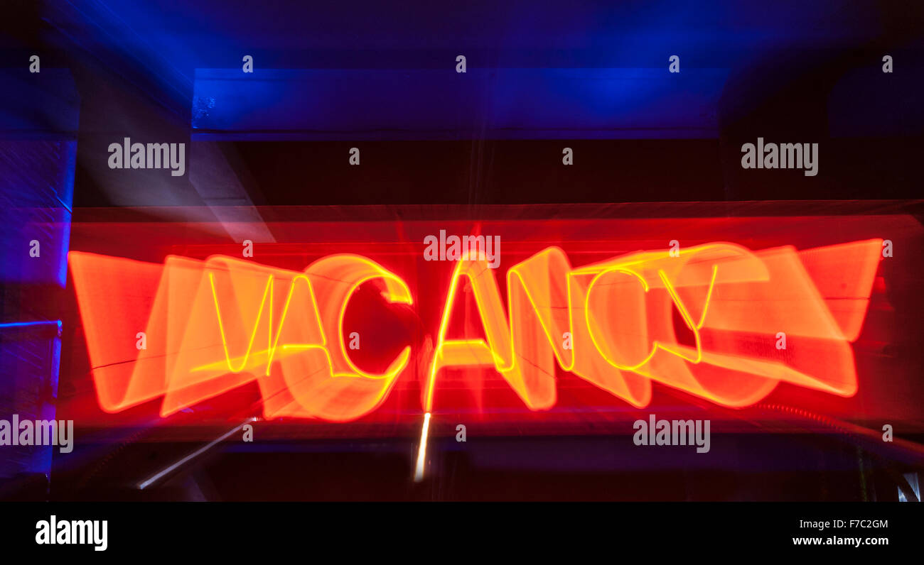 red neon vacancy sign for motel motion blur effect on dark blue background. - Stock Image