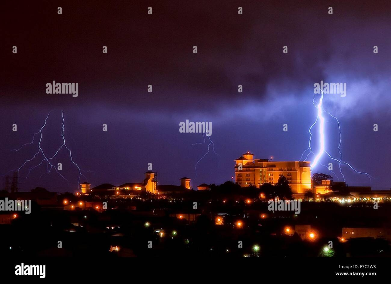 Fork lightning over a city at night - Stock Image