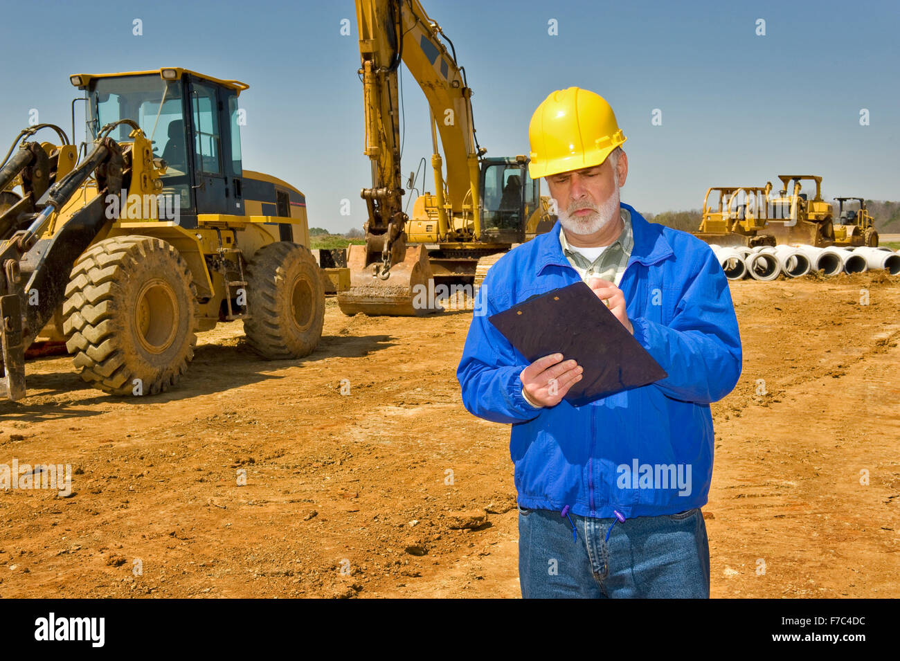 Foreman With Clipboard and Highway Construction Equipment - Stock Image