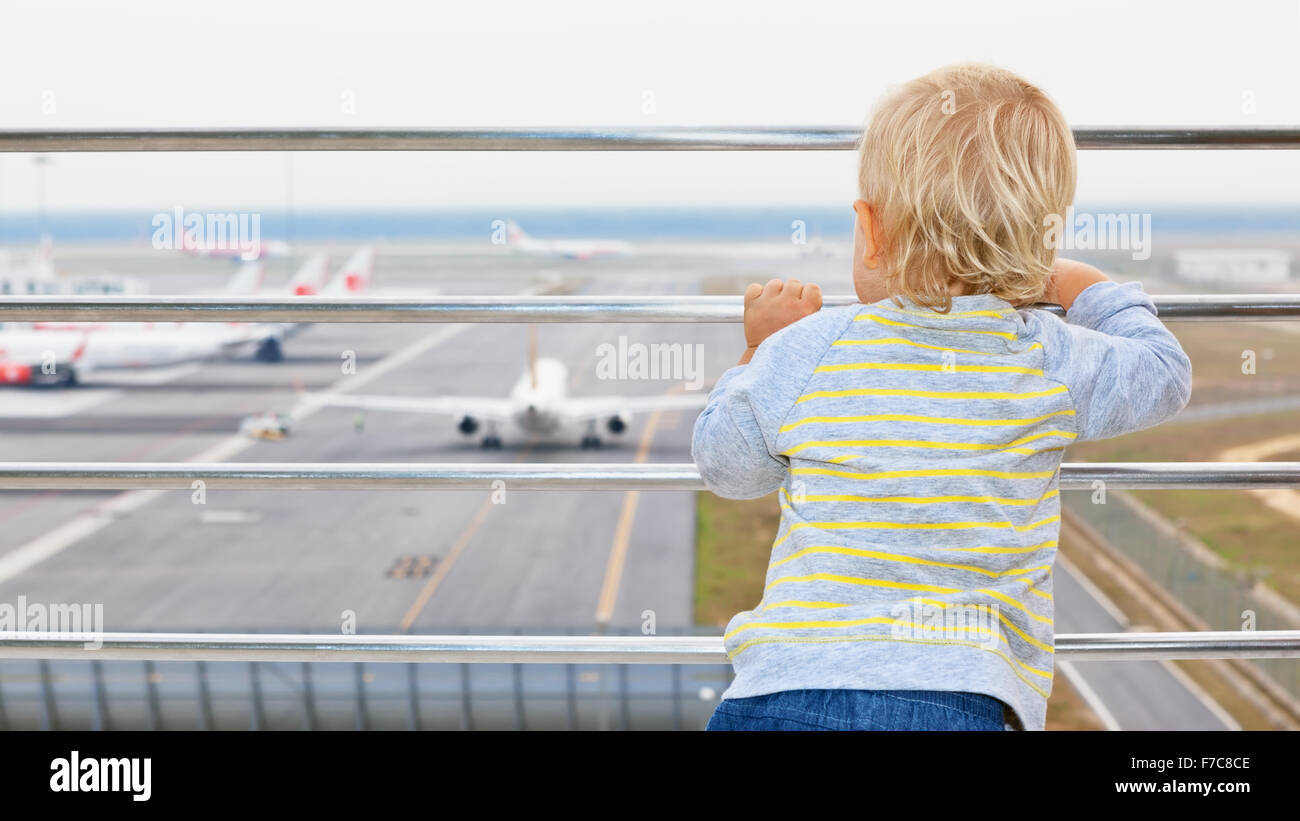 Little baby boy waiting for boarding to flight in airport transit hall and looking at airplane near departure gate - Stock Image