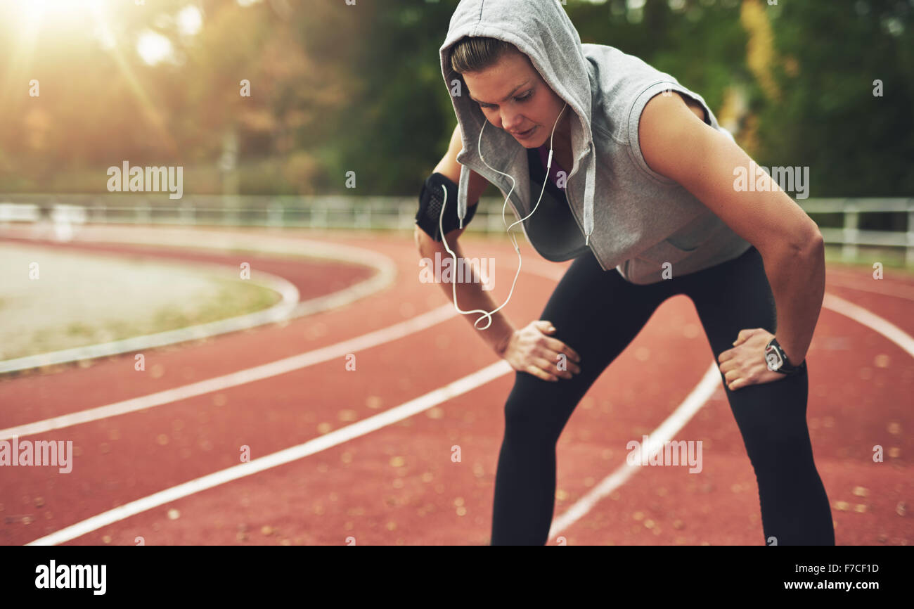 Young sportswoman standing on stadium and listening to music, looking down - Stock Image