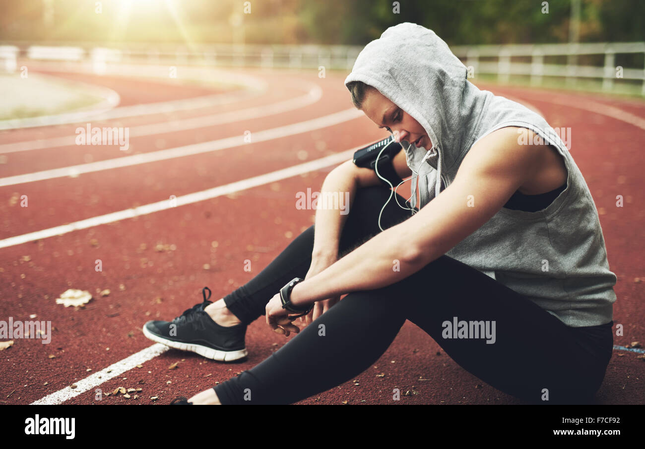 Young woman in sportswear sitting on stadium, listening to music and preparing for training - Stock Image