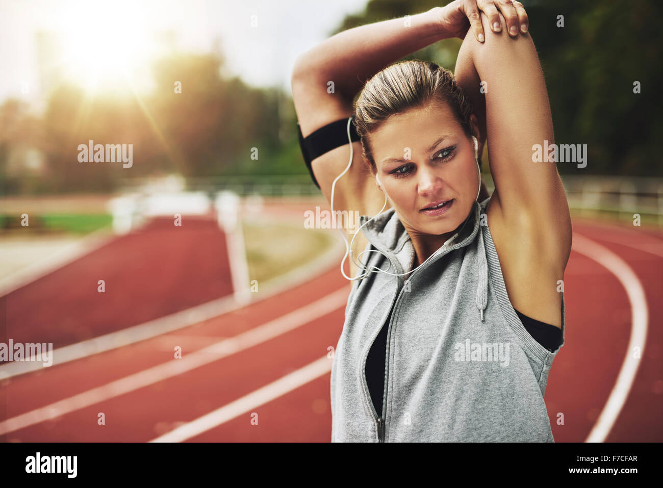 Fit young woman stretching her arms before training. Concentrated - Stock Image