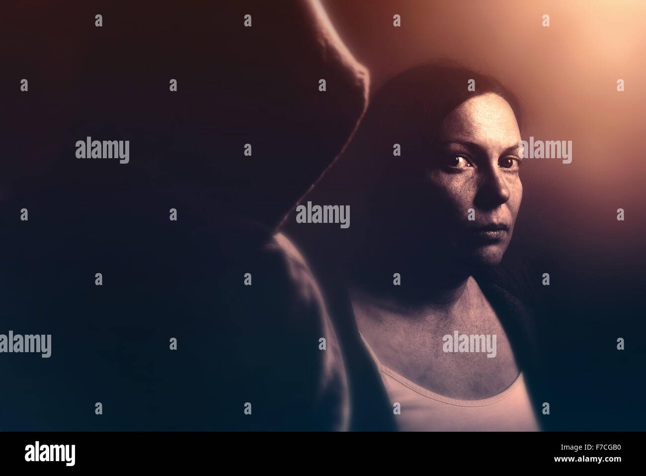 Stalker concept, intense low key portrait of woman being stalked, retro toned image with selective focus - Stock Image