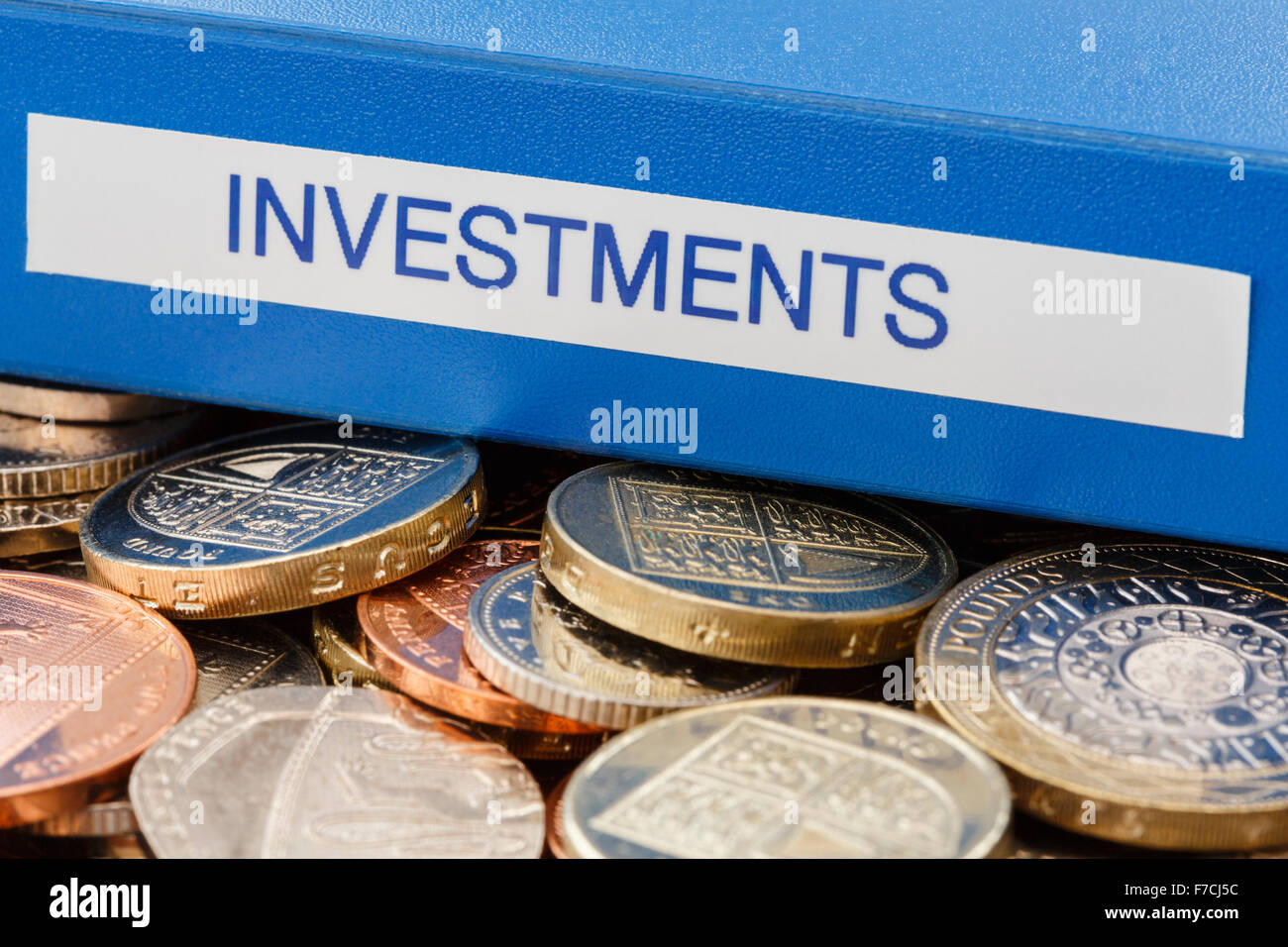 Investments folder on a pile of English sterling old £ pound coins to illustrate investing money in stocks - Stock Image