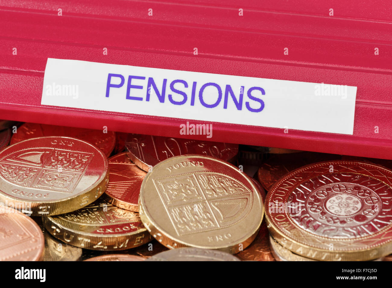 Pensions portfolio on a pile of sterling pound coins to illustrate investing money for retirement planning and pension - Stock Image