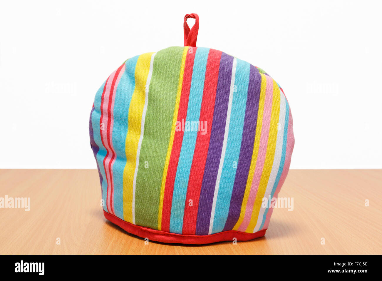 Colourful striped teacosy covering a teapot to keep it warm on a wooden table. England UK Britain - Stock Image