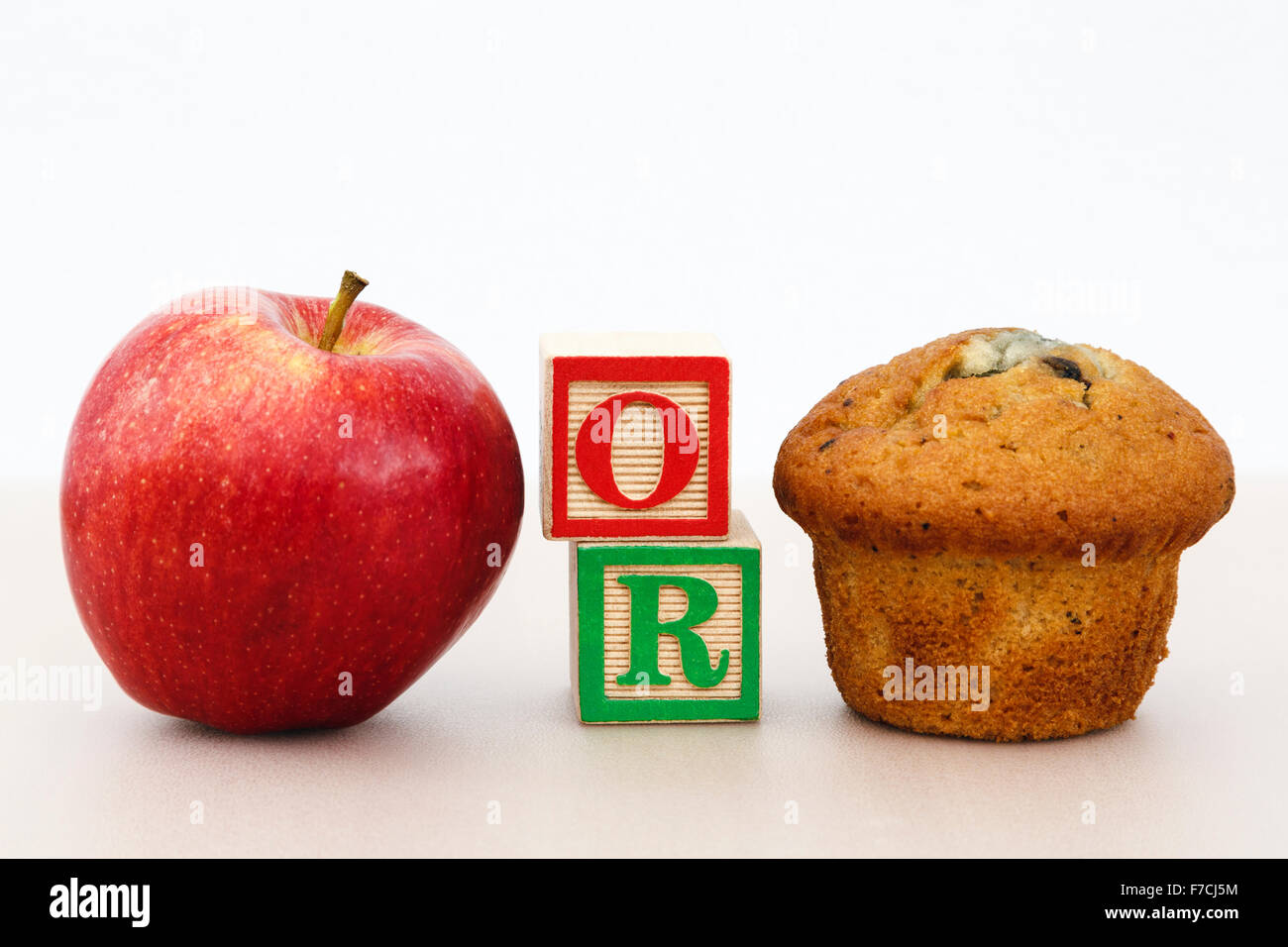 Rosy red apple and a muffin cake with word OR in letter blocks on a tabletop to illustrate choice of healthy or - Stock Image