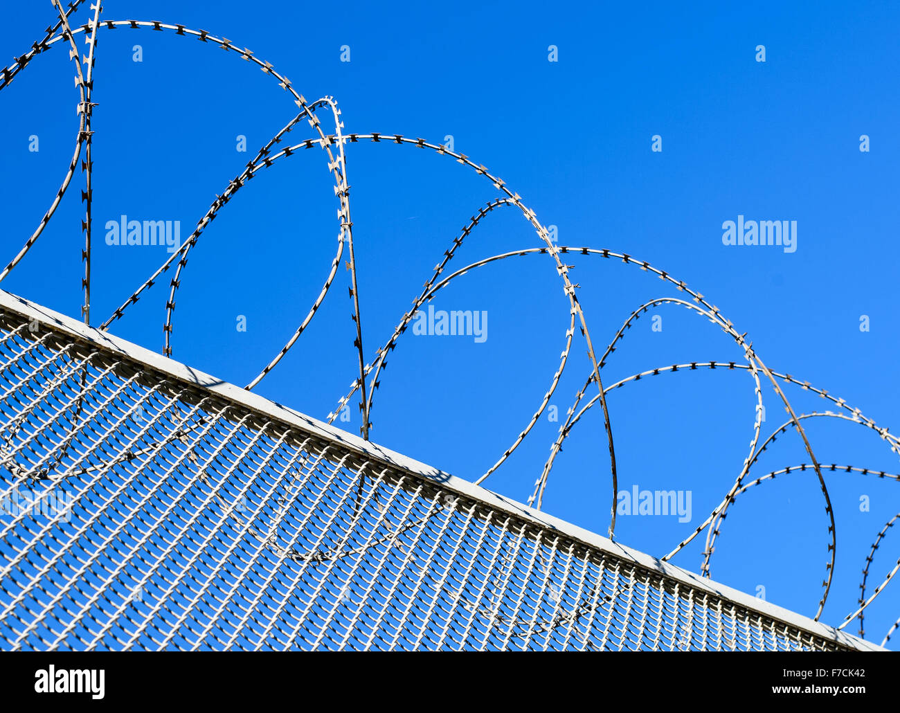Fence with a barbed wire against the blue sky. Illustration of the concept of freedom or liberty. - Stock Image