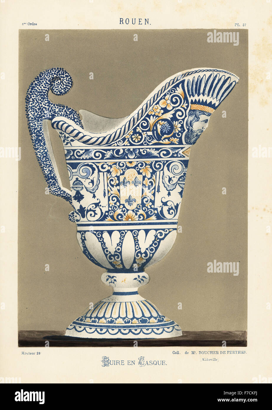Ceramic ewer in the shape of a helmet, Rouen, France. Decorated with fleur de lys, a man's head, foliage in blue Stock Photo