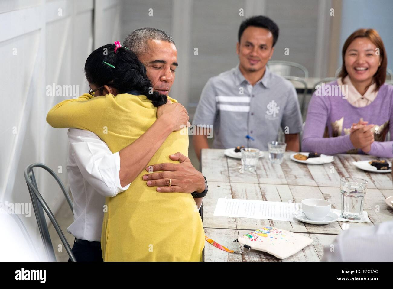 U.S. President Barack Obama is hugged by a young girl during a tour of the Dignity for Children Foundation November - Stock Image