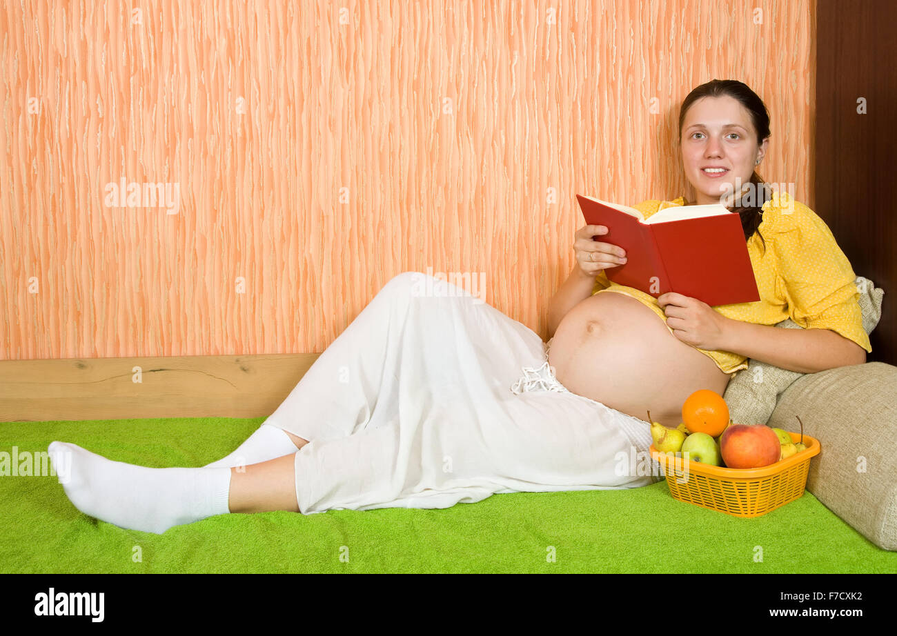 pregnant woman lying on sofa in livingroom with book Stock Photo