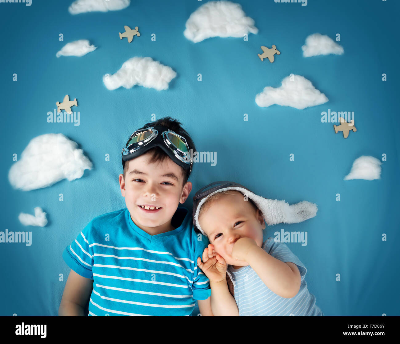 Two boys lying on blanket with white clouds - Stock Image
