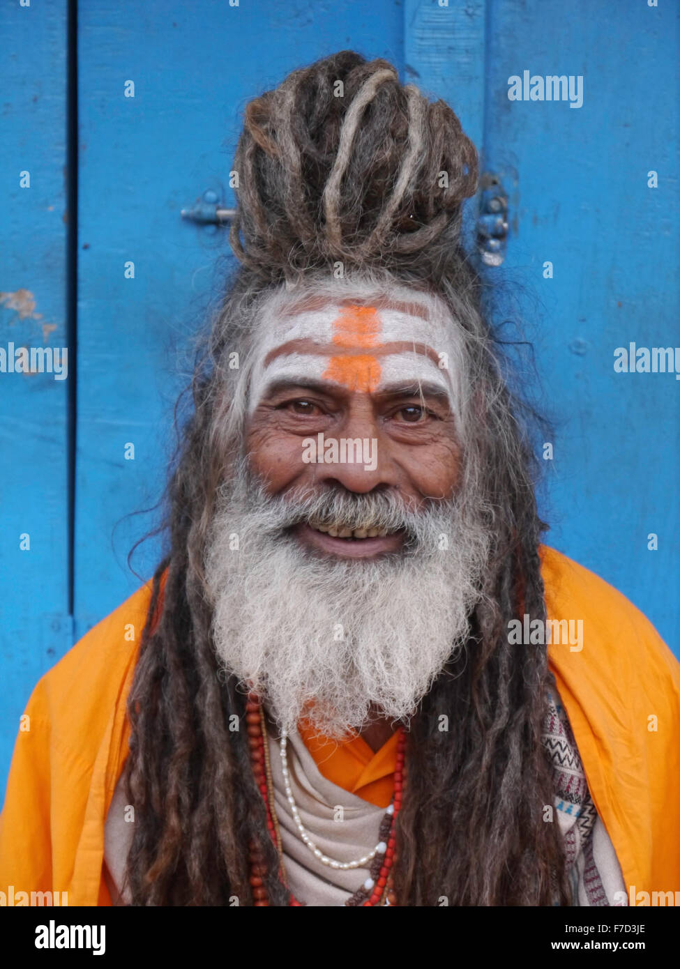 Portrait of a Sadu . Smiling image of holy man dressed in vivid contrasting  colours of orange and blue . - Stock Image