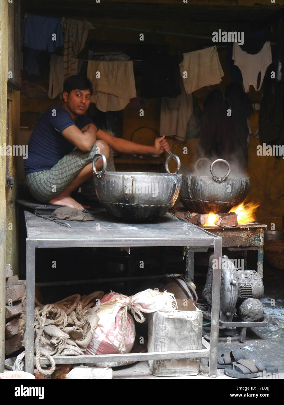Market trader  crouches down to stir the metal cauldrons full of hot boiling water - food preparation.   Jaipur - Stock Image