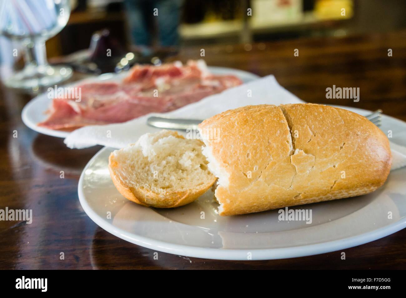 Freshly baked bread roll with Spanish ham (Jamón ibérico, Iberian ham, pata negra) cured ham served as - Stock Image