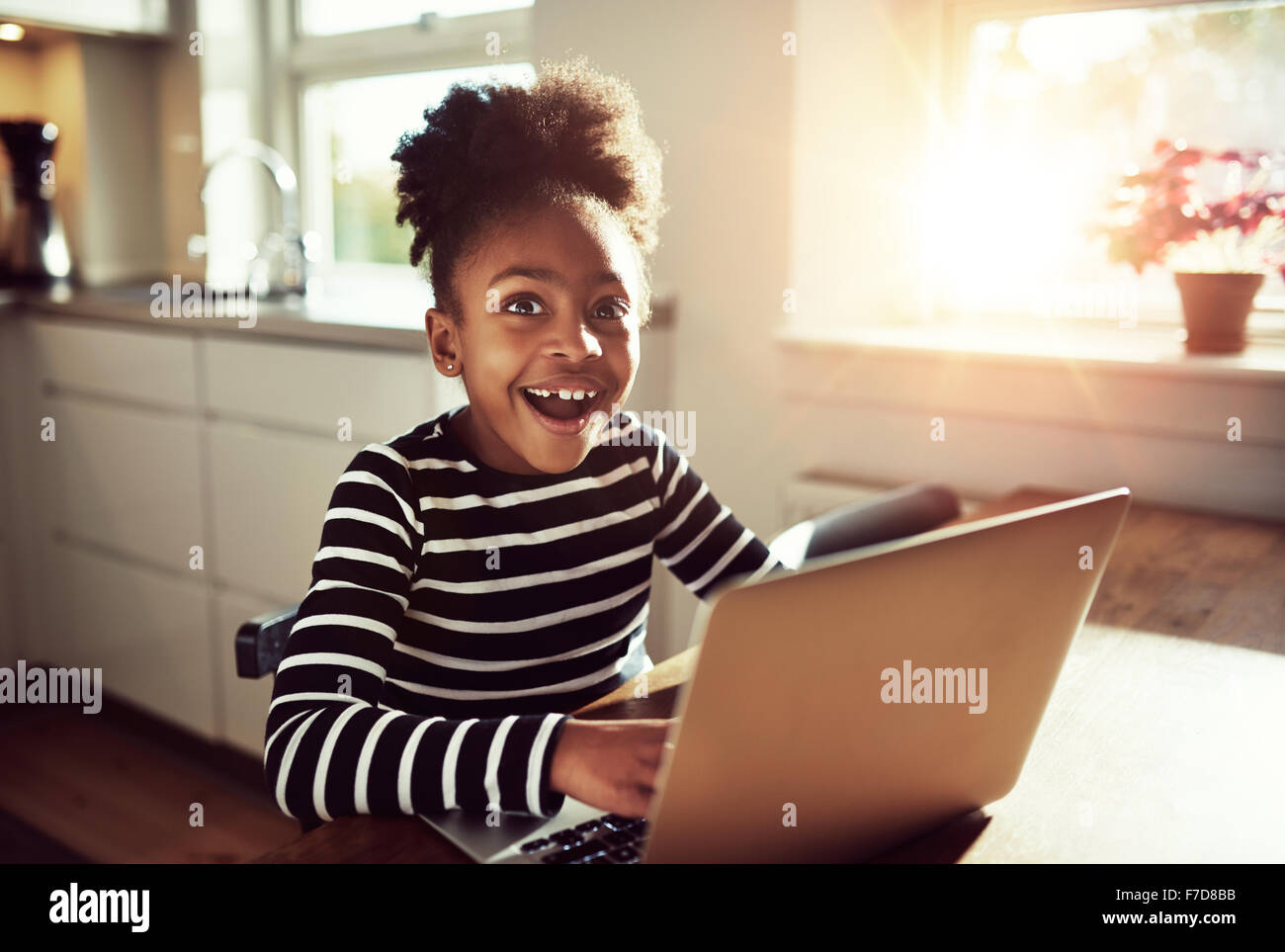 Black girl sitting playing on a laptop computer at home looking at the camera with a joyful expression of amazement - Stock Image