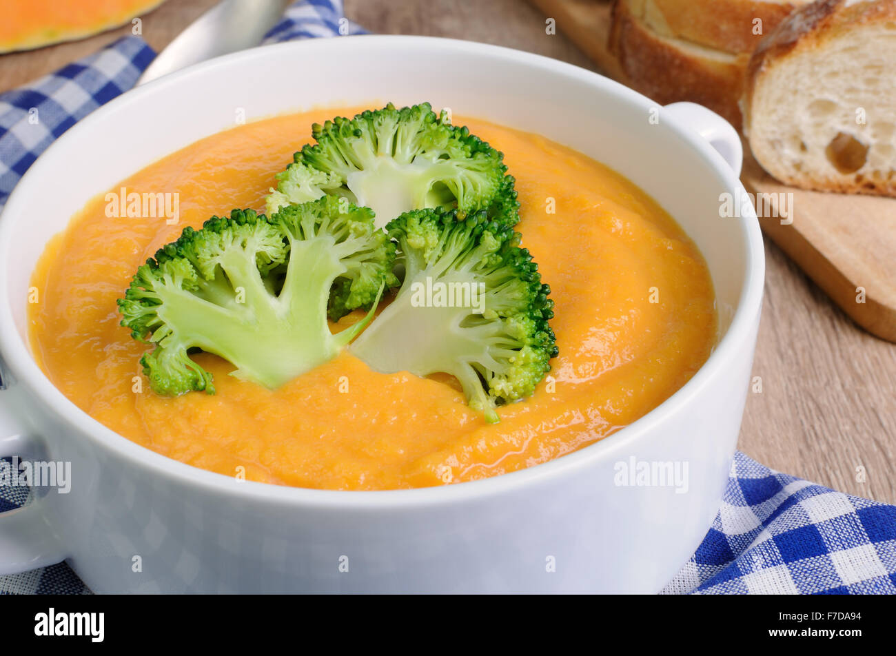 Pumpkin puree soup with cream and parsley on soup plate close-up - Stock Image