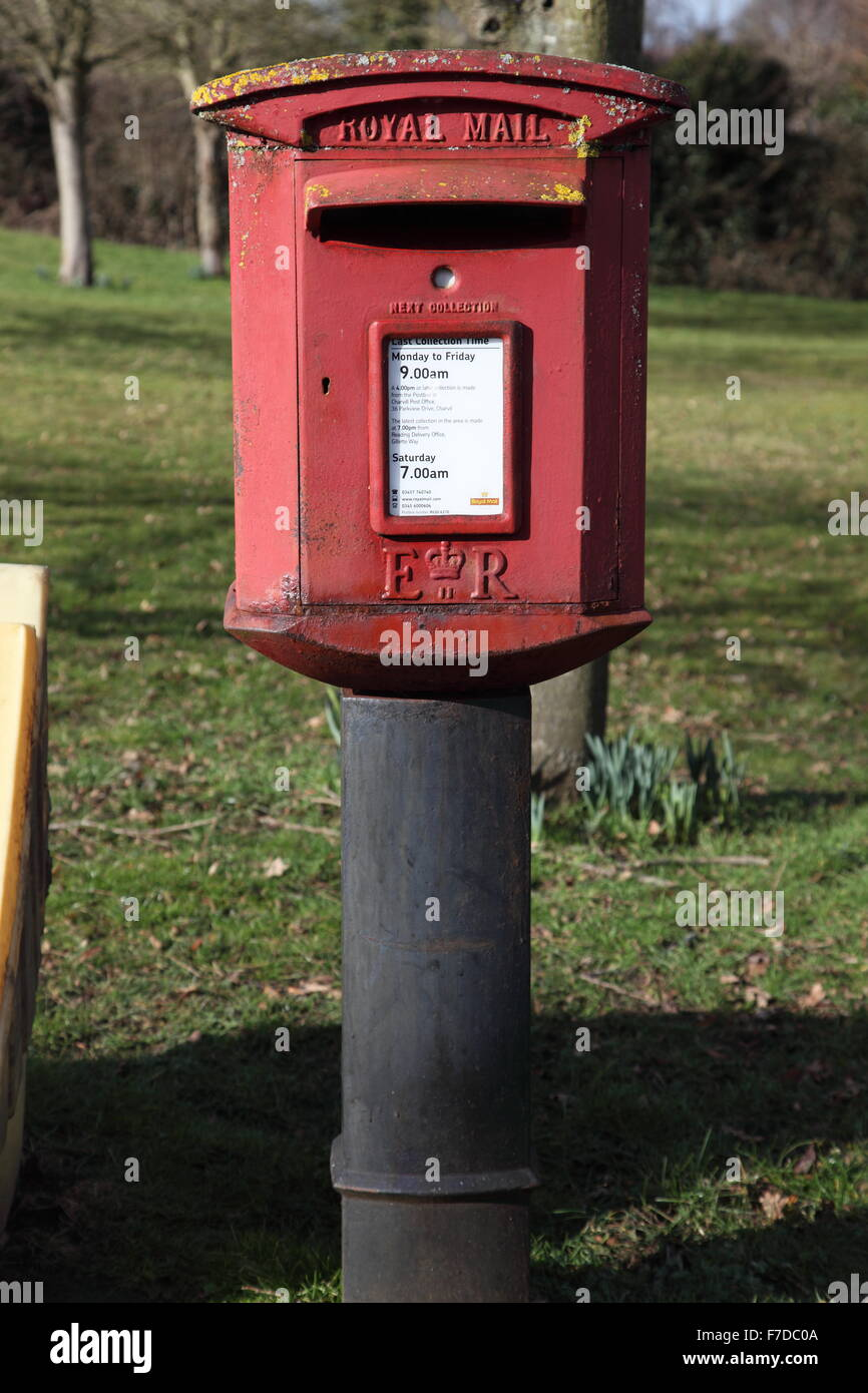 A large Red painted Letter box mounted on a pillar (pillar box) at the side of a road showing details of posting - Stock Image