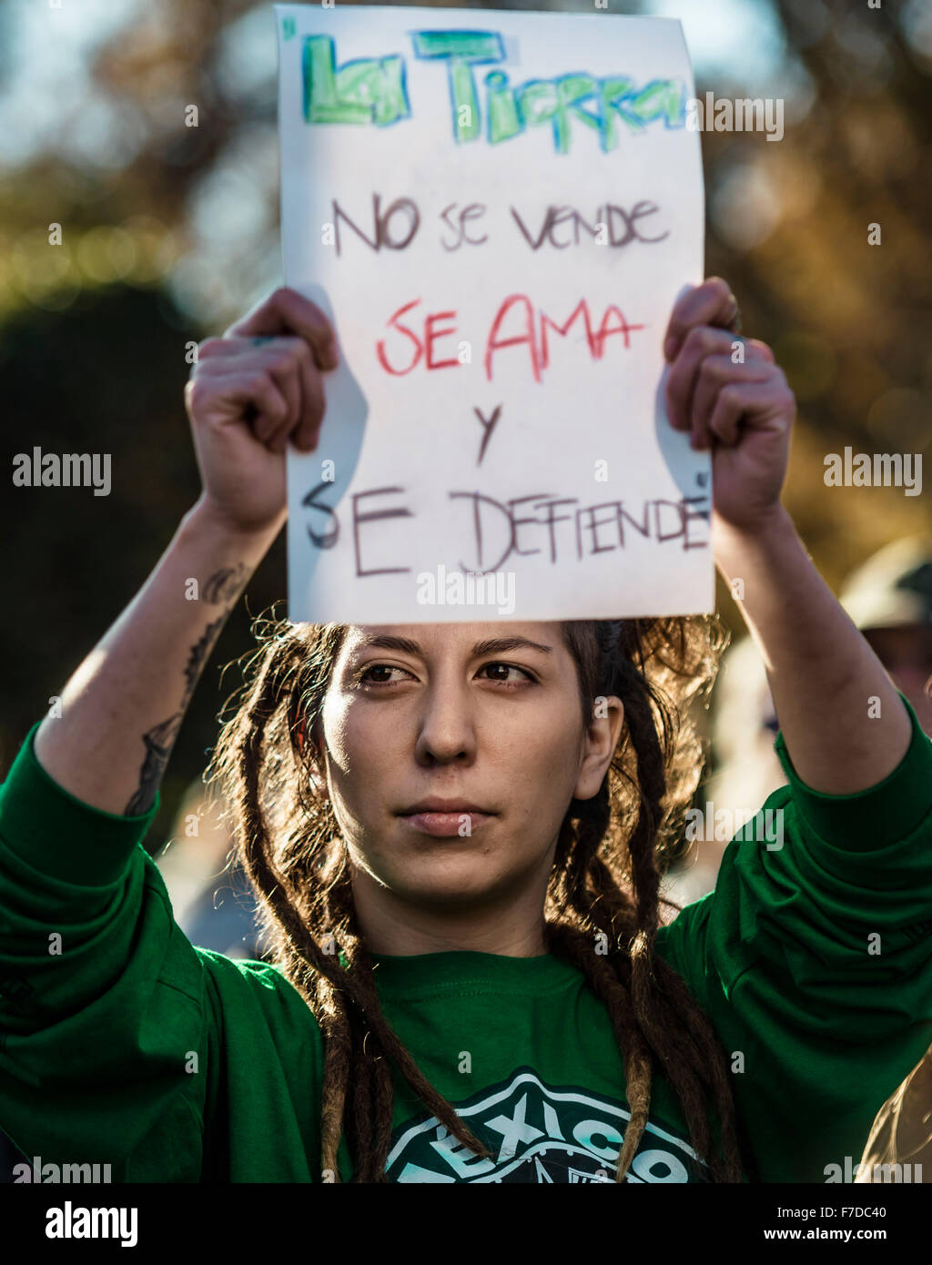 Barcelona, Spain. 29th November, 2015. A protestor against global warming holds her placard reading 'The earth - Stock Image