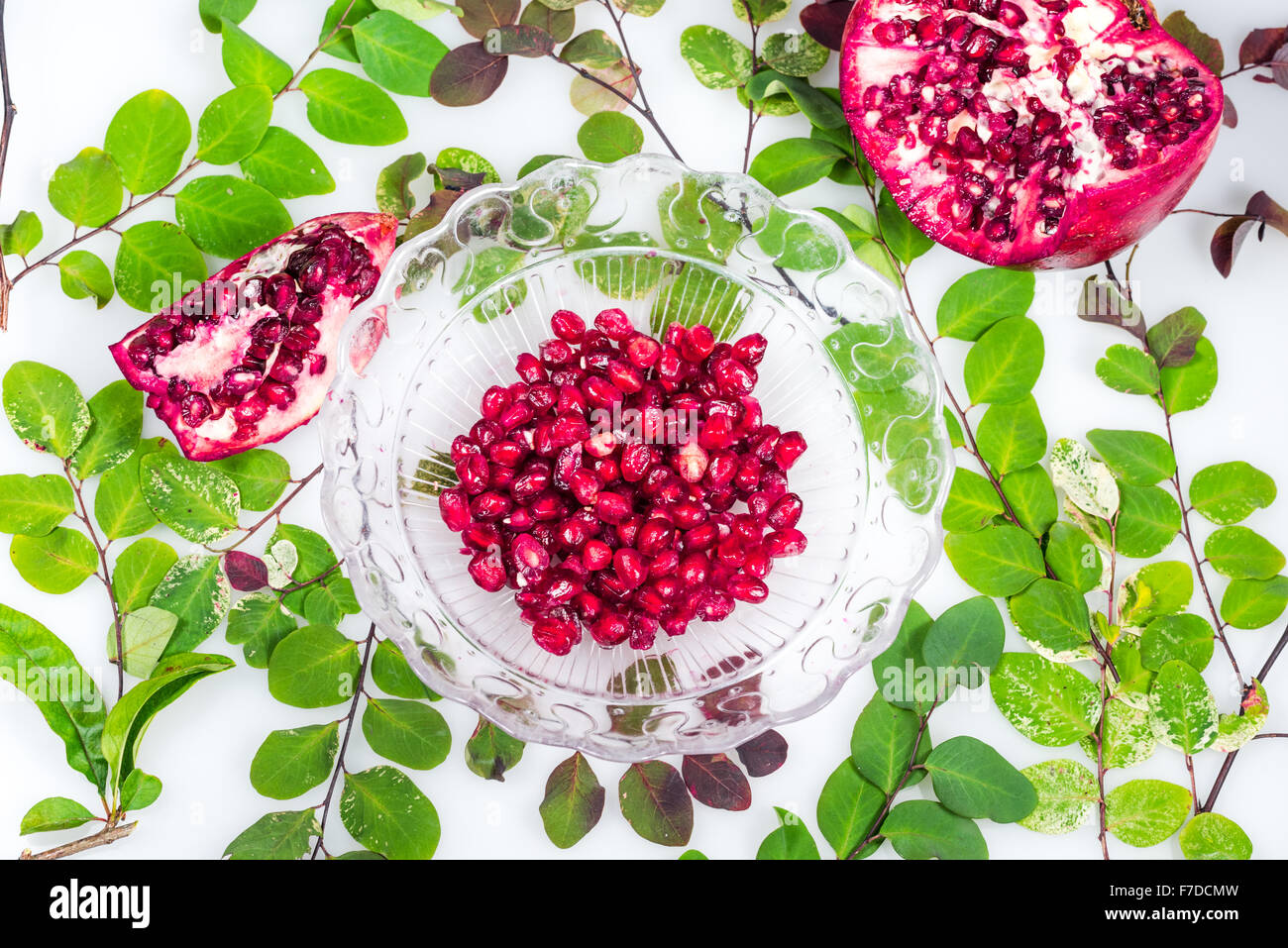 Pomegranate Seed in the bowl and green leaves - Stock Image