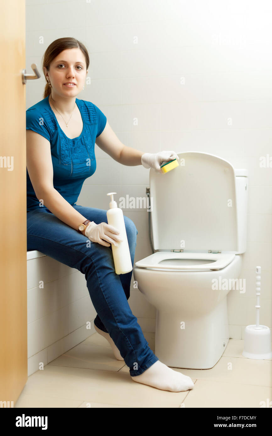 Woman Cleaning Toilet Bowl With Sponge In Bathroom