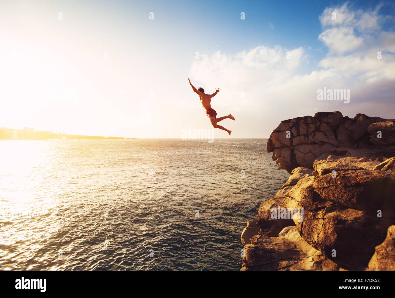 Cliff Jumping into the Ocean at Sunset, Summer Fun Lifestyle Stock Photo