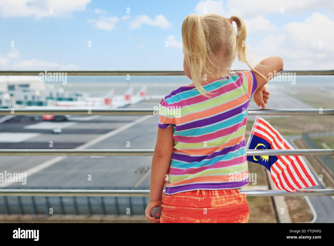 Little child waiting for boarding to flight in airport transit hall and looking at airplanes near departure gates - Stock Image