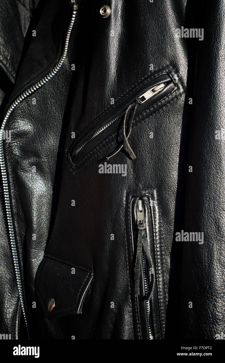 A worn classic black leather motorcycle jacket in sunshine showing zippered pockets and change pocket with flap. - Stock Image