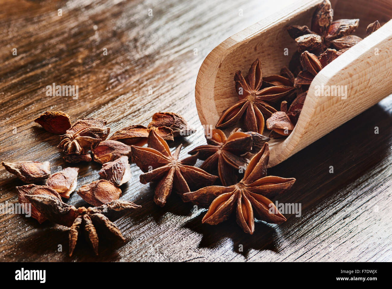 Star anise on wooden spoon on wooden table - Stock Image